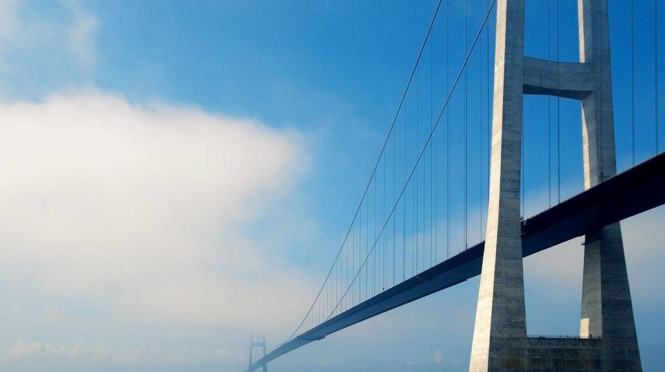 """Die hoch über dem Meer erbaute Storebaeltbrücke führt durch die Meerenge Großer Belt und verbindet die dänischen Inseln Fünen und Seeland. Mit einer Hauptspannweite von 1624 Metern gehört sie zu den längsten Hängebrücken der Welt. Evonik's ökozertifiziertes Hydrophobierungsmittel Protectosil® BHN, das mit dem Gütezeichen """"Instandsetzungsprodukt"""" ausgezeichnet wurde, verleiht dieser kombinierten Eisenbahn- und Strassenbrücke, die besonders intensiven Witterungsbedingungen ausgesetzt ist, eine schützende Imprägnierung, die Wasser und darin gelöste Schadstoffe abweist."""